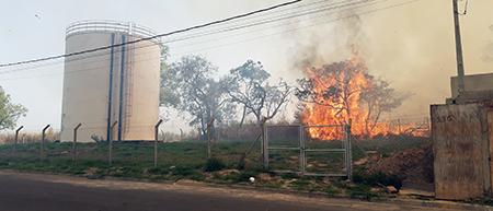 Bombeiros lutam, na tarde de hoje, dia 14, para evitar que incêndio atinja casas na Vila Martins